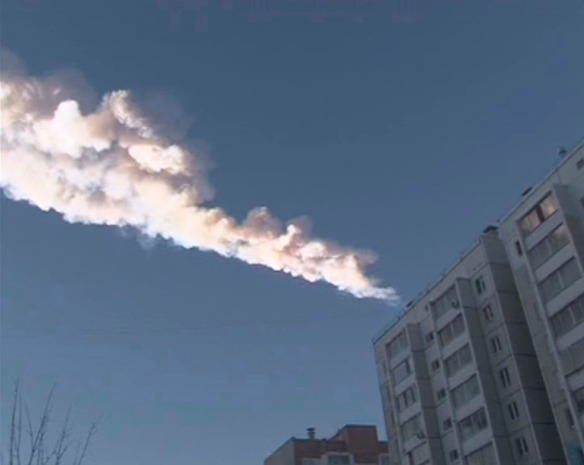 Still image from video shows the trail of a falling object above a residential apartment block in the Urals city of Chelyabinsk